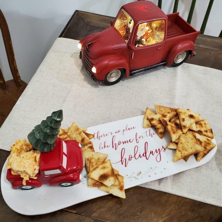 "Holiday cheese and crackers tray with ""There's no place like home for the holidays"" sentiment. Pickup truck holds cheese spread. Utensil for spreading cheese is topped by Christmas tree. Vintage red pickup truck with glitter globe Santa cab also on table for 2020 Christmas trends."