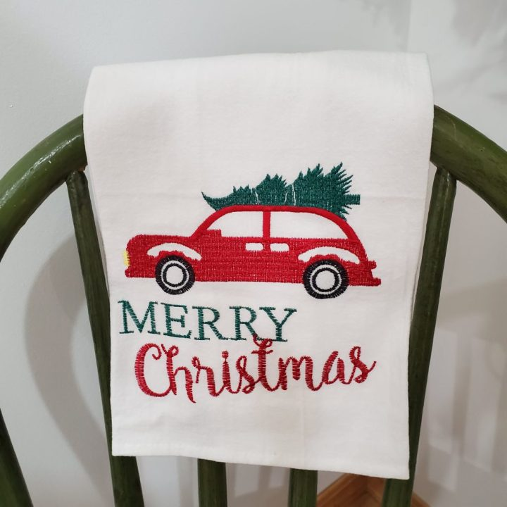 Merry Christmas white kitchen towel hanging over the back of a green spindle chair. Old red car stitched on towel with Christmas tree on top of car.