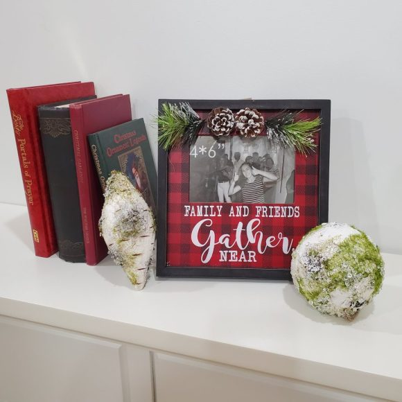 Buffalo plaid family and friends photo frame on a white fireplace mantel surrounded by a birch ornament on either side and four books standing on the left.