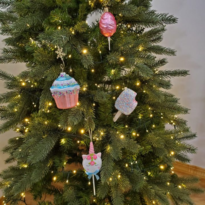 Christmas tree lit with warm white rice lights and decorated with candy ornaments in pastels for Christmas trends 2020.