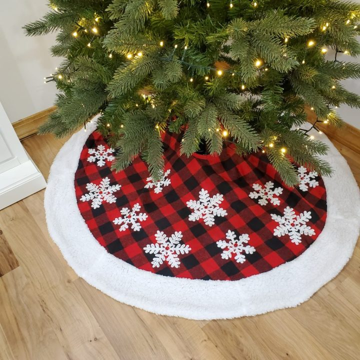 A buffalo plaid tree skirt trimmed with white plush and topped with white snowflakes graces the bottom of a Christmas tree for Christmas trends 2020.