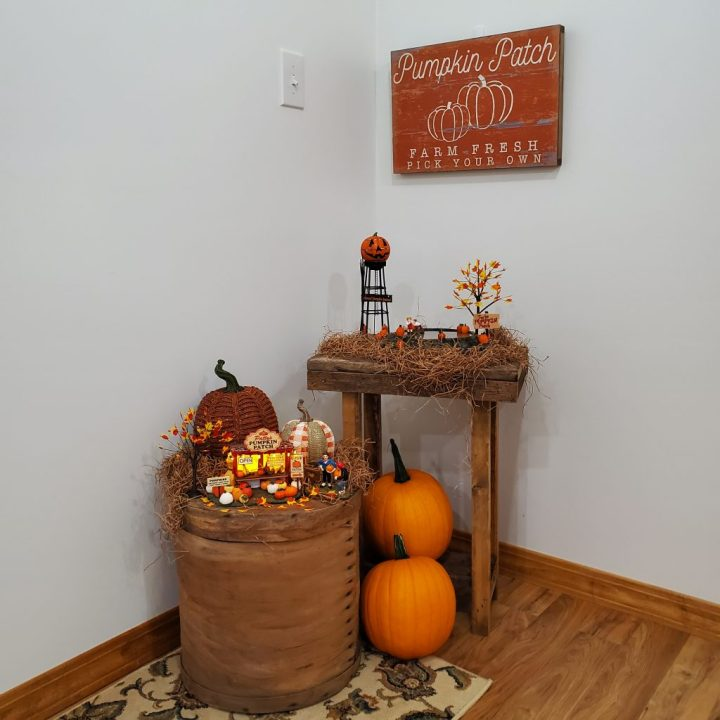 Decorating for fall with Department 56 with Patty's Pumpkin Patch on  light brown filler grass on a vintage cheese box with resin pumpkins, Animated Pumpkin Patch and  Halloween Water Tower on a taller side table with light brown filler grass, a rustic orange and white pumpkin patch sign hanging above on the wall and two real pumpkins at the base of the table and next to the cheese box.