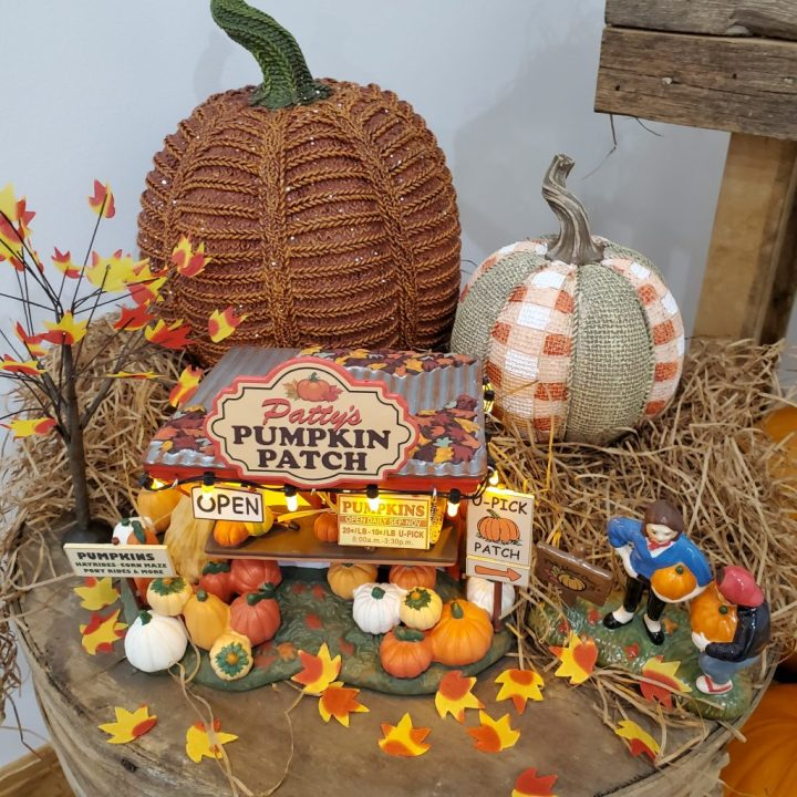 Decorating for fall with Department 56 taking a close-up look at Patty's Pumpkin Patch on top of a vintage cheese box covered with light brown filler grass, tiny silk covered leaves and two resin pumpkins.