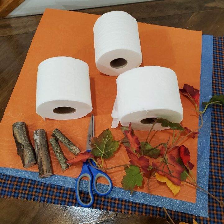 Supplies on table for DIY toilet paper roll pumpkins includes three squares of fabric, three rolls of toilet paper, scissors, 3-inch and 4-inch cut pieces of branch, and leaf strands from fall garland.