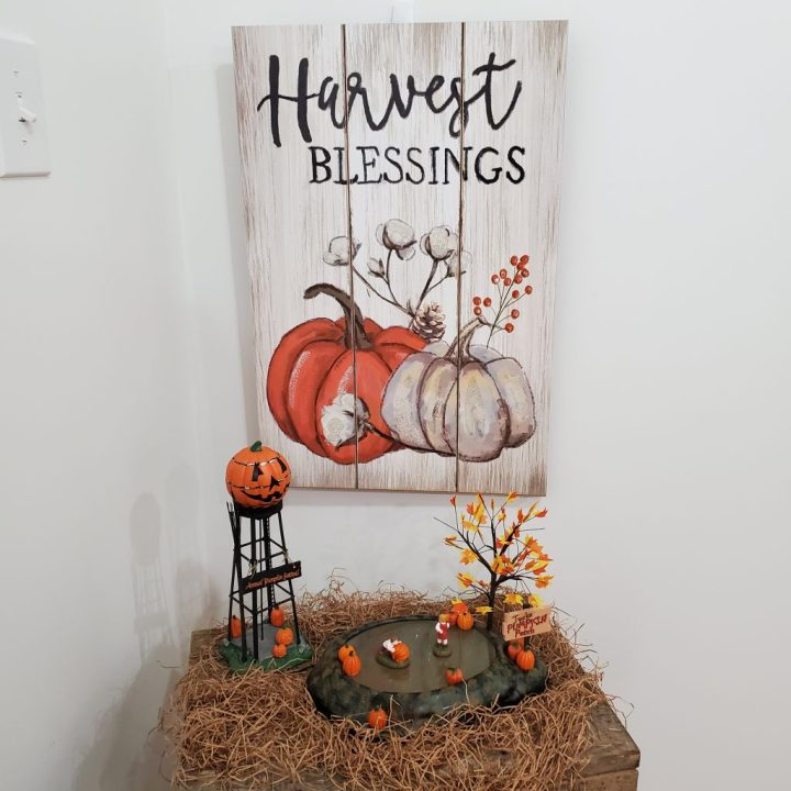 Washed white Harvest Blessings wall art with pumpkin art on wall behind Halloween Water Tower and Animated Pumpkin Patch on light brown filler grass on rustic barn wood side table as I'm decorating for fall with Department 56.
