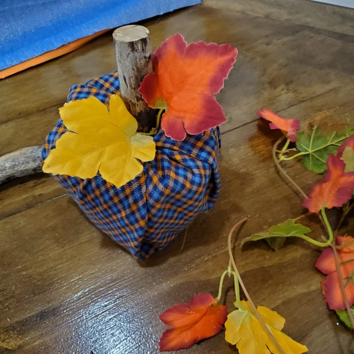 Completed navy, sky blue and orange plaid DIY toilet paper roll pumpkin with branch piece for stem and a strand of two fall leaves sits on table with additional leaves, fabric squares, and a branch stem.