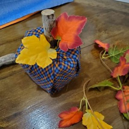 Completed DIY toilet-paper-roll pumpkin craft. Pumpkin sits on wooden table surrounded by silk leaves, fabric pieces and a branch stem. The toilet paper roll has been wrapped in a navy, sky blue and orange flannel fabric and topped with two silk, fall red and orange leaves along with a stem made from a branch.