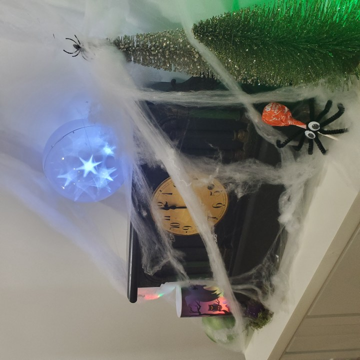 Decorating tip for Halloween to use Spider Sucker craft in a white fireplace mantle display with a black mantel clock set to midnight, a Krypton green shatter proof ornament and Halloween projector on one side, sparkly green trees on the other and topped with a sphere with white phasing effect