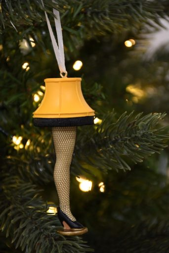 "Resin leg lamp ornament from the movie ""A Christmas Story"" hanging on a lighted tree"