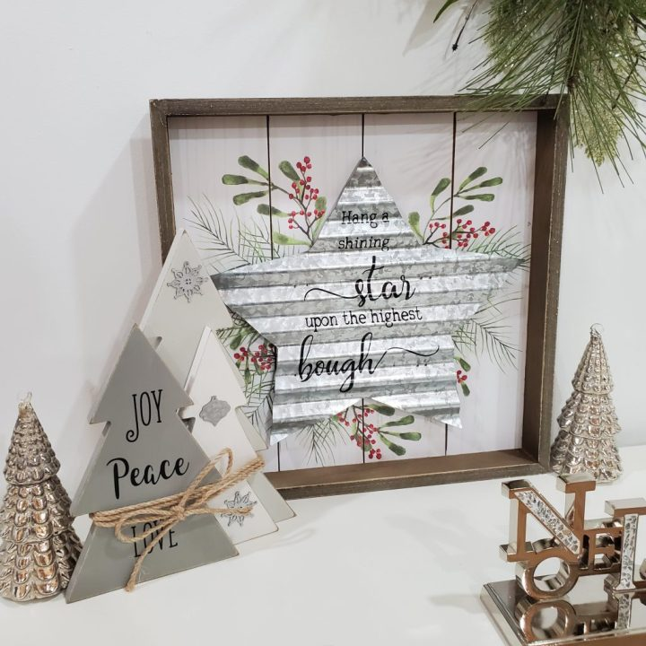 """Fireplace or tabletop display featuring gray 2021 Christmas trends with gray metal trees, gray wooden trees wrapped with twine, wall art with a gray steel star, and a gray glitz """"Noel"""" stocking hanger."""