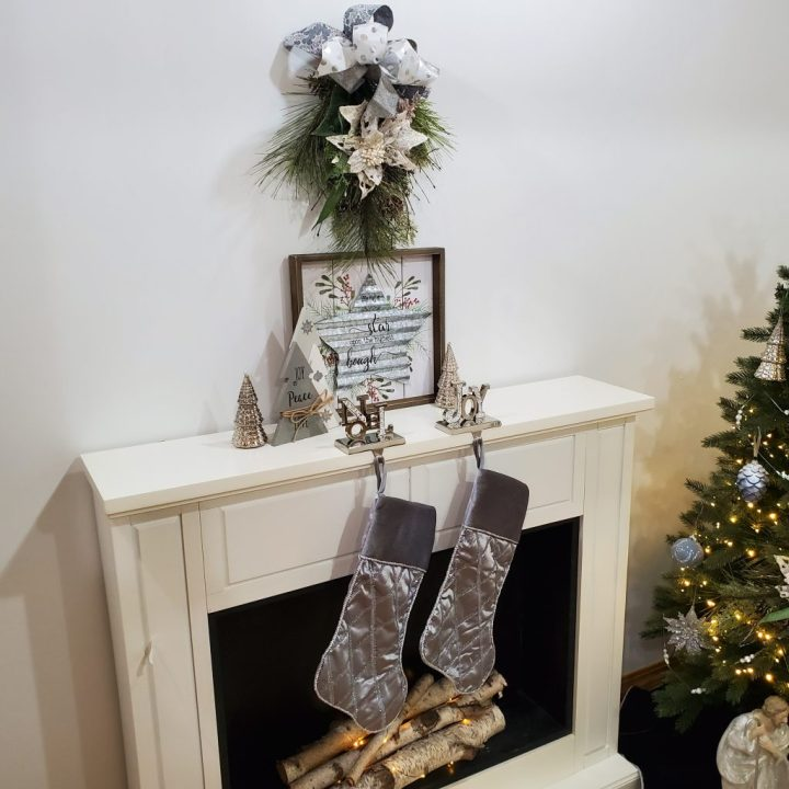 White fireplace with gray poinsettia and ribbon swag hanging above it. Mantel topped with silver metal star wall art, wood trees wrapped with twine, mercury-glass look trees and silver silk stockings hanging from silver glitz Noel and Joy stocking holders. Part of tree decorated in gray with touches of blue shows on right.