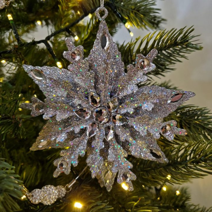 Silver sparkle snowflake with beads hanging with gem ball glass garland from evergreen tree lit with clear lights.