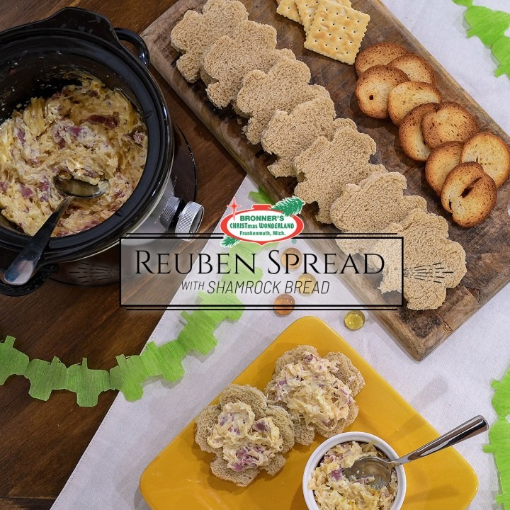 Reuben spread is on the table along with a board of bread, crackers and chips. A bright gold plate holds a personal serving of warm reuben spread recipe.