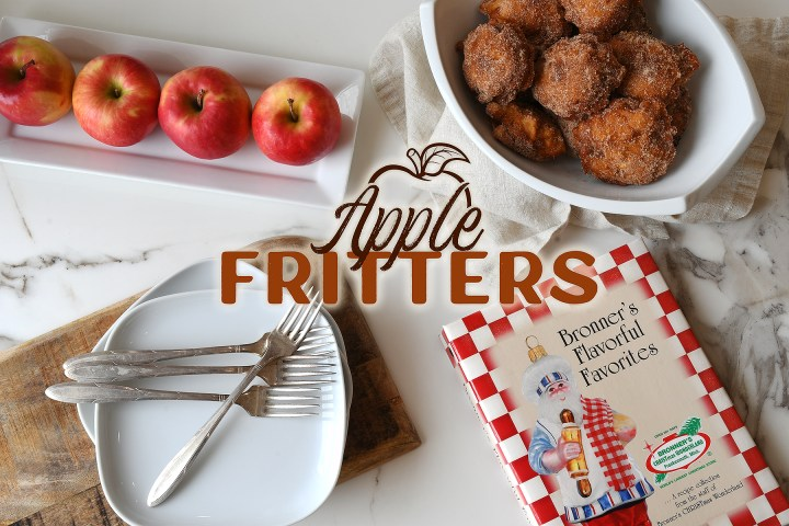 """Tabletop with apple fritters in a bowl, fresh apples lined up on a plate, """"Bronner's Flavorful Favorites"""" staff cookbook and a charcuterie board,  topped with white serving plates and forks, all for our apple fritters recipe"""