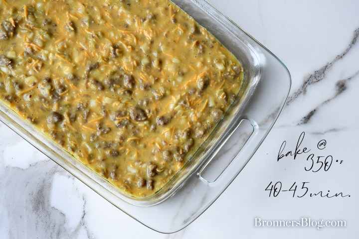 The breakfast casserole is in a clear glass 9-by-13-inch dish on the white and black granite table top and ready to bake at 350°F for 40-45 minutes.