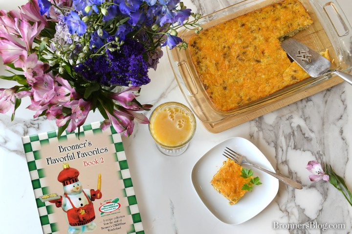The breakfast casserole is on the white and black granite-top table with a small white plates, silver forks and a bouquet of purple flowers in a vase.