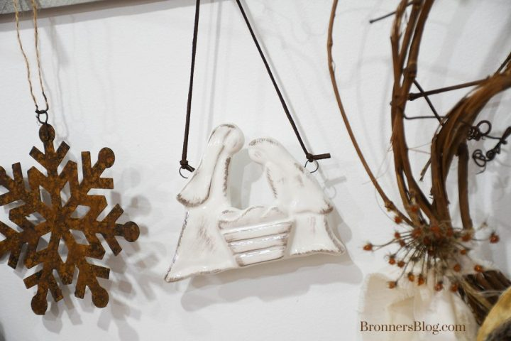 A closeup of the peg board features the ceramic Holy Family ornament, rusted metal snowflake ornament and edge of the grapevine wreath.