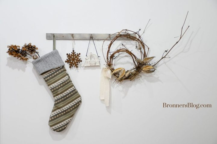 A knit Christmas stocking, rusted metal snowflake ornament, ceramic Holy Family ornament and grapevine wreath hang from a peg board.
