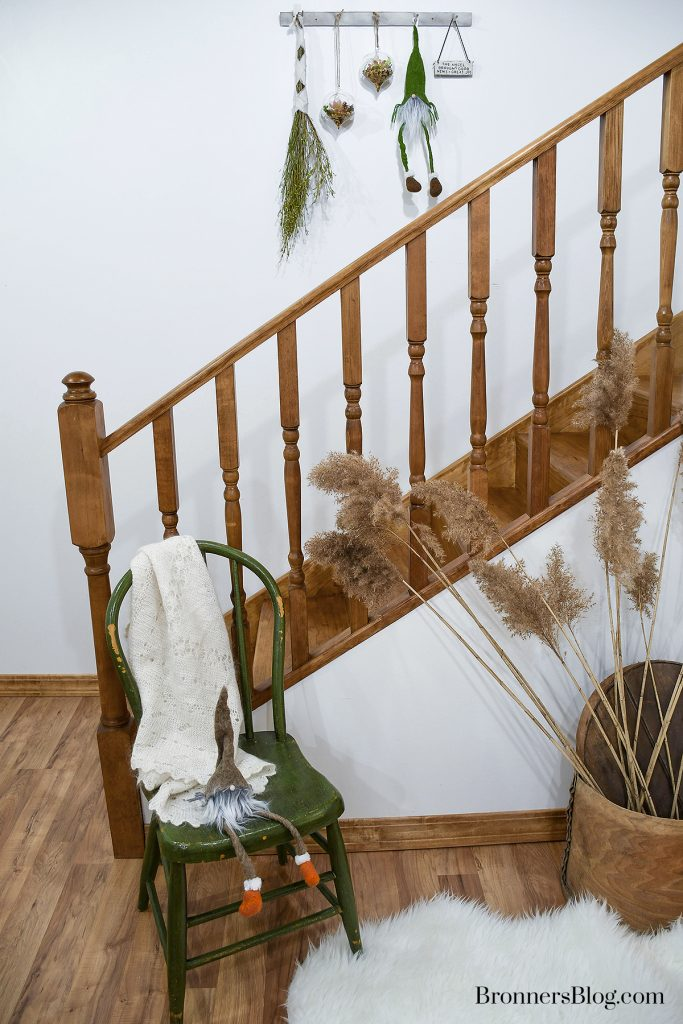 A peg board with natural decor for Christmas features a wrapped bundle of dried flowers, two succulent glass teardrop ornaments, a troll,, and a ceramic ornament with a Christmas message. In from of the stairway is a wooden chair  with a troll seated on the edge and a wooden cheese box with wild pampas grass.