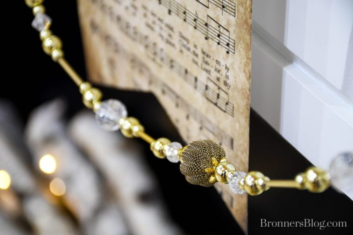 "Closeup of the silver and gold bead garland and vintage-look ""Silent Night"" sheet music draped along the front of the mantel."