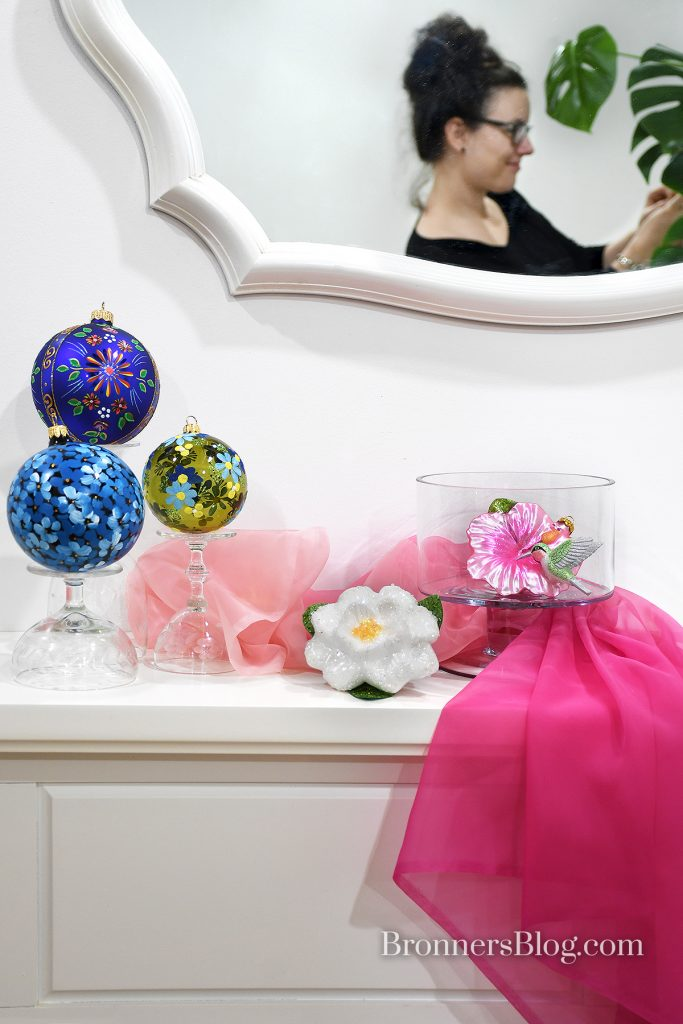 Display on white fireplace mantle of three blue and green floral round ornaments on upside-down stem glassware. Next to them is a white flower clip on the mantle next to a pink flower and hummingbird clip ornament in a small, clear trifle dish, all softly draped in sheer, soft pink fabric.