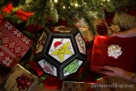 Christmas-Themed pentagon die beneath a tree with presents