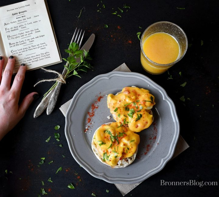 eggs del monico plated with silverware, a glass of orange juice and an open book of table prayers