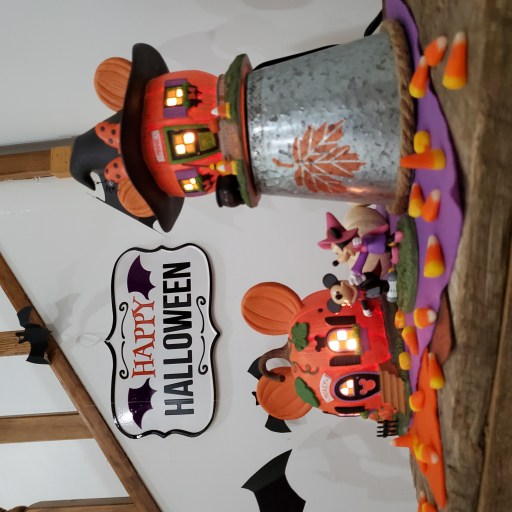 Closeup of Mickey's and Minnie's Pumpkintown Houses on a tabletop display  with colored felt, candy corn and mini pumpkins.
