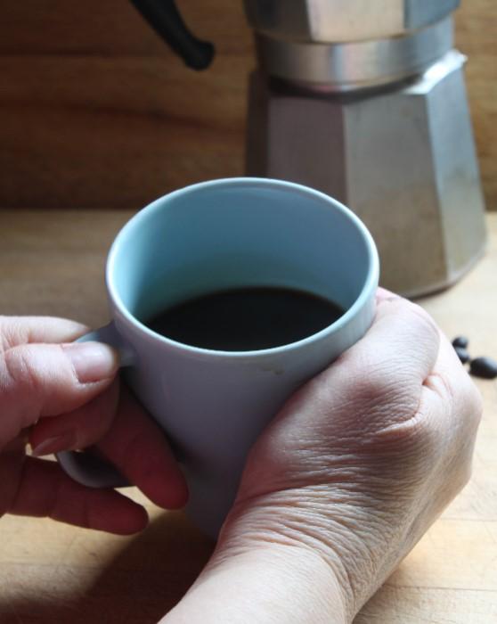 hands holding coffee cup with moka in background by doris lovadina-lee