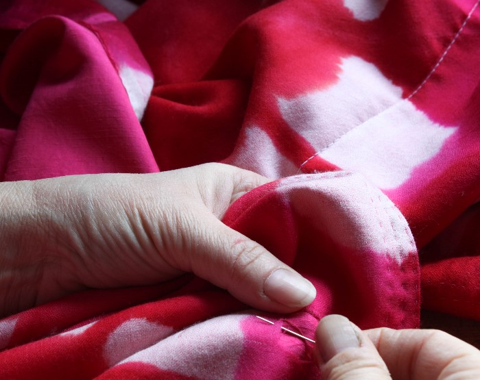 hands stitching a fuchsia red scarf doris lovadina lee