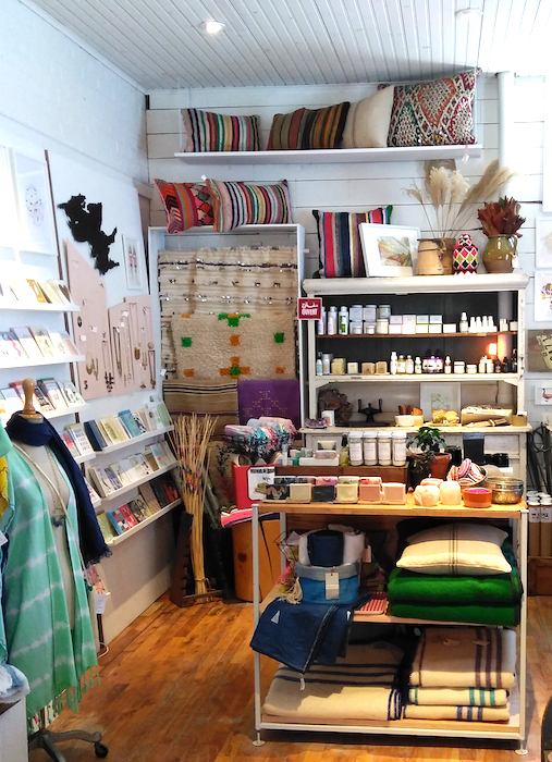 scarves, blankets, pillows and cards on display in back of Kokito store, locally made artisan shop
