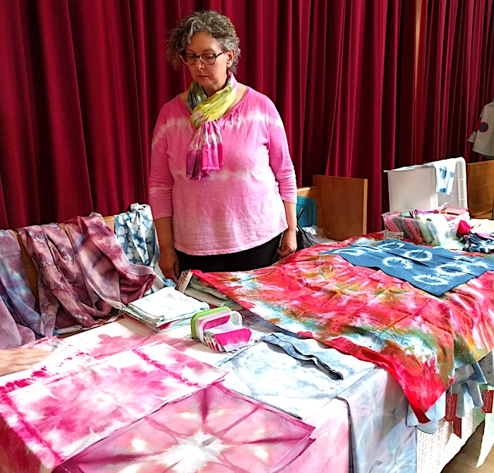 Doris Lovadina-Lee behind table with hand dyed fabric and snow dyed scarves at the Toronto Modern Quilt Guild meeting June 2018
