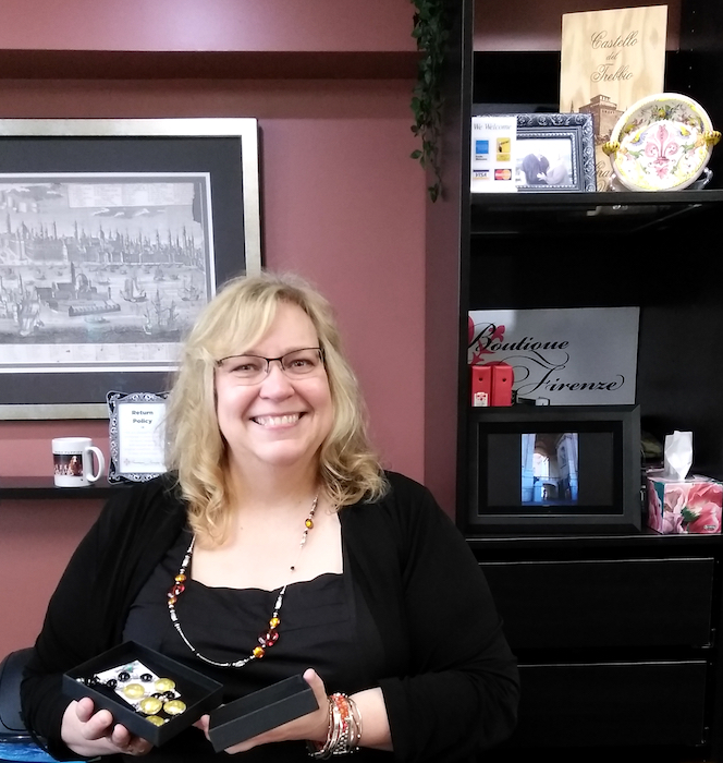 Boutique Firenze owner Bettina in her shop London Ontario Canada holding a box with black and gold venetian glass necklace