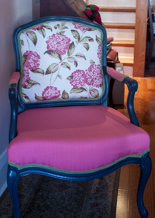 floral and solid upholstered chair in front of staircase