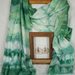 green ombre stripe scarf draped over a frame with smaller frame holding pair of hand crocheted cream earrings