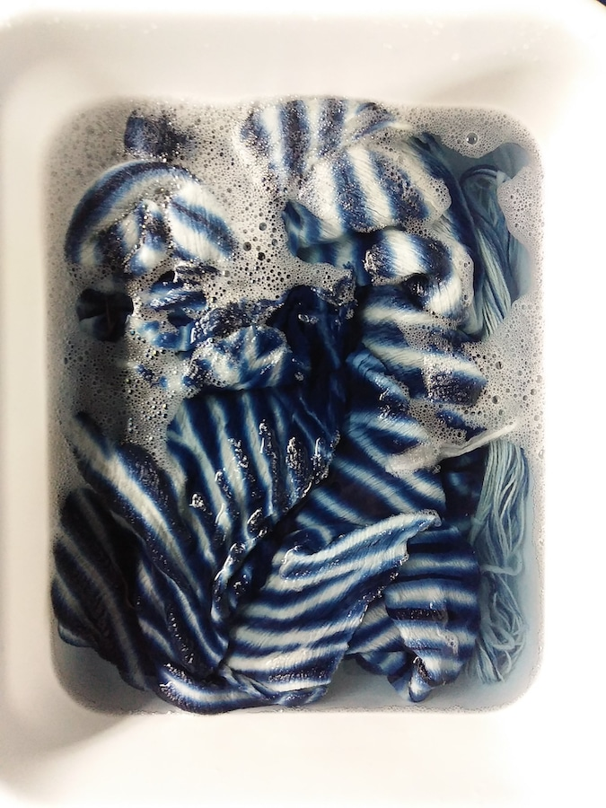 indigo striped fabric in tub of soapy water by doris lovadinalee toronto textile artist