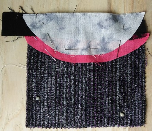 black sparkly fabric with curved grey and red half circles and a black strip a stitch meditation unfinished