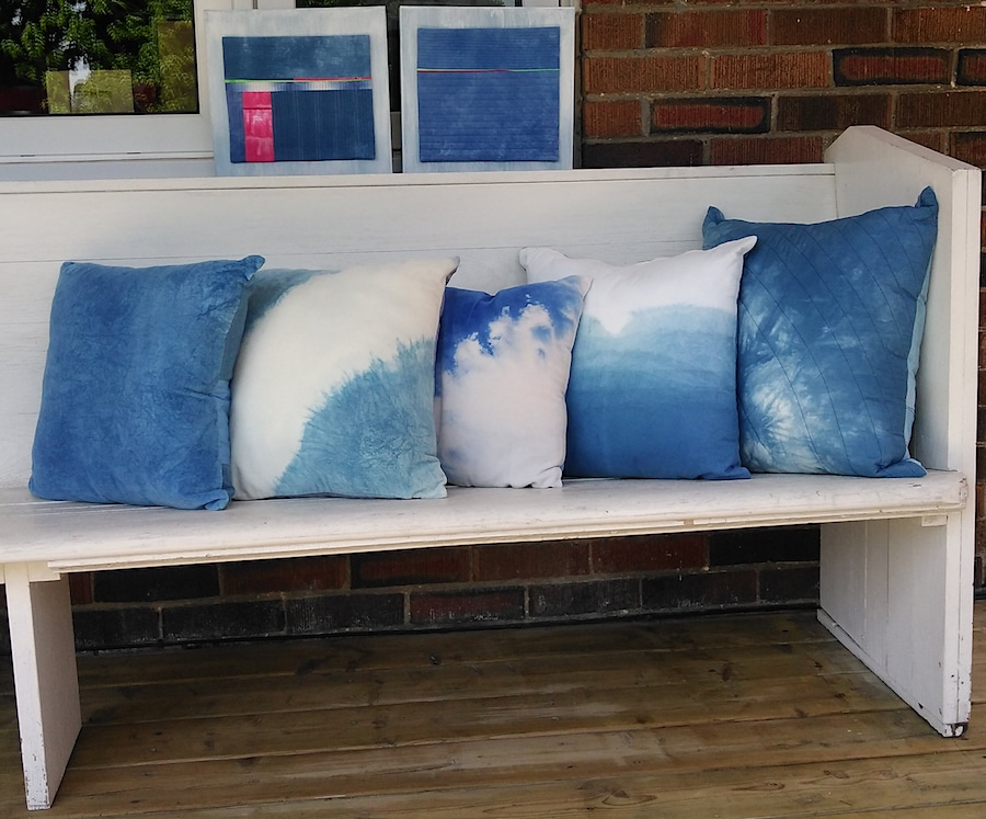 5 hand dyed pillows on white bench and 2 textile paintings