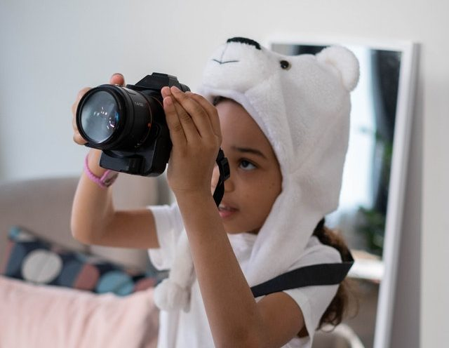 preschool Afro American girl holding a camera exploring her passion and interests through experiential learning