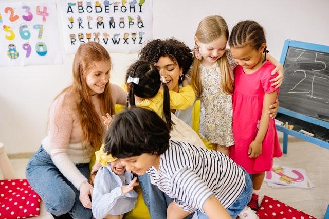 diverse nursery preschool  teachers bonding with happy children