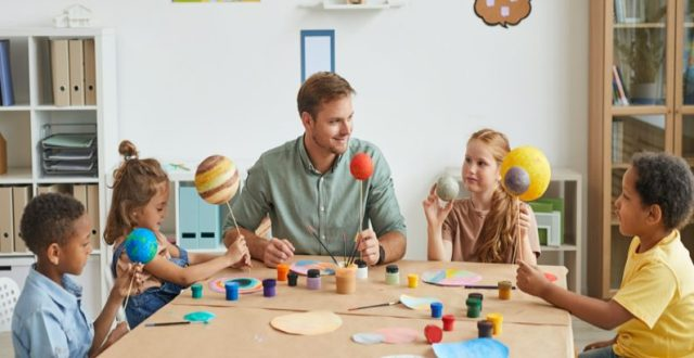male caucasian teacher in the classroom with group of children at the table offering experiential learning activities exploring planets, arts & crafts