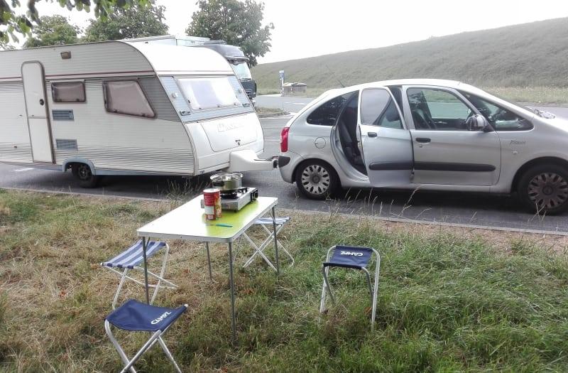 Parada con la caravana para comer. Mesa y sillas plegables de camping.