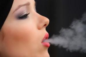 Femme qui expire de la fumée de cigarette