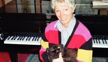 Ada Gentile seduta davanti al pianoforte con il gatto in braccio