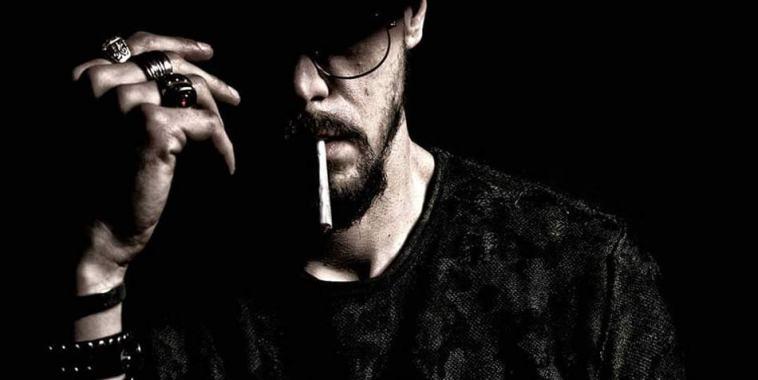 Fabbrostik su fondo nero, cappello in testa, sigaretta in bocca e braccio tatuato
