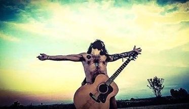 GRAY Renda a braccia aperte con la chitarra, a torso scoperto in mezzo ad un campo