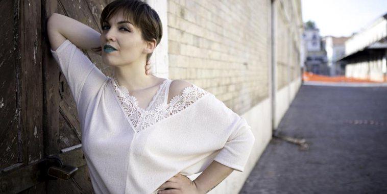Larèt vestita di bianco appoggiata sul gomito ad un muro
