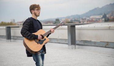 Alessandro Angelone con la chitarra e alle spalle delle montagne