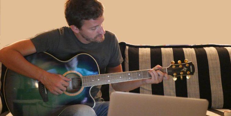 Gambo (Marco Speroni) sul divano con la chitarra