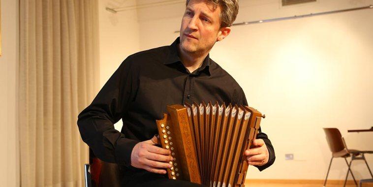 Corrado Rojac vestito di nero e seduto, mentre suona l'armonica a mantice di Greggiati